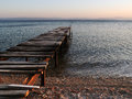 Old broken wooden pier on sunset enters the calm sea fishing boat in the distance quiet minutes after end of the summer season Royalty Free Stock Image