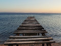 Old broken wooden pier on sunset enters the calm sea fishing boat in the distance quiet minutes after end of the summer season Royalty Free Stock Photo