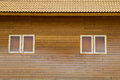 Old brown clay tiles roof pattern with small windows on wood wal Royalty Free Stock Photo