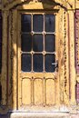 Old brown peeling door. There are black panels on the door. The sun is shining on the door Royalty Free Stock Photo