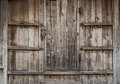 Old brown wooden door embedded in ages wood wall Royalty Free Stock Photo