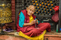 Old buddhist nun sits and begs in Kathmandu, Nepal