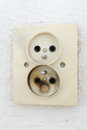 Old burnt plug in a wall Royalty Free Stock Photo