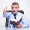 Old business man with book shows thumb up senior bussines in hand and looks at the camera on gray background Stock Photos