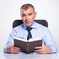 Old business man holds a book at his desk senior bussines sitting the and holding while looking the camera isolated on white Stock Photography