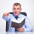 Old business man pointig while holding book senior bussines sitting at the desk with a in his hand and pointing and looking at the Stock Photos