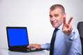 Old business man shows victory at laptop senior bussines sitting his with a blue screen and showing sign while smiling to the Royalty Free Stock Image