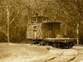 Old caboose in sepia tone on track under trees Royalty Free Stock Photo