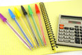 Old calculator and color pens on the yellow writing book Stock Photos