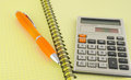 Old calculator and pen on the yellow writing book Royalty Free Stock Images