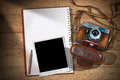Old camera instant photo frame and notebook vintage with leather case empty with pencil an on a wooden table Stock Image