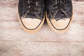 Old canvas shoes on wooden background Stock Photography