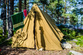 Old canvas tent stands in a pine forest on the island Royalty Free Stock Photo