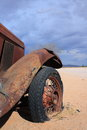 Old car with flat tire an brown rusty in the desert of namibia in the village sollitaire clouded sky Stock Photo