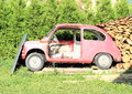 An old car red standing on the grass being covered by wood Stock Images