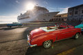 Old car on street of Havana at sunrise with cruise ship in backg Royalty Free Stock Photo