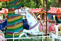 Old carousel in a holiday park with beautiful white horse close up Royalty Free Stock Photo