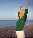 Old caucasian woman exercising outdoors to stay fit portrait of beautiful mature practicing yoga on beach with copyspace Stock Photo