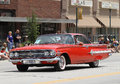 Old chevrolet car in parade in small town america bright red antique a summer while a crowd watches on and an brick building is Stock Photography