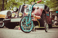 Old children`s tricycle on a background of vintage car.