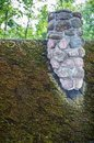 Old chimney made of rocks on the mossy roof Stock Image