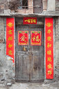 Old Chinese door with peeling fortune posters Royalty Free Stock Photo