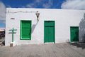 Old church with green doors on a white wall in lanzarote spain Stock Photo