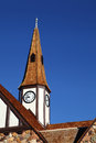 Old church steeple with clock against a clear blue sky Stock Photo