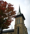 Old church steeple an tree in autumn splendor accents a yellow brick century Royalty Free Stock Photography