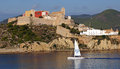 Old city in ibiza boat sails past the set on the shore of the mediterranean sea amid the rolling green hills Stock Photo