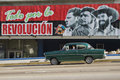 Old claaic car driving by propoganda sign havana cuba december classic a todo por la revolucion meaning all for the revolution and Stock Image