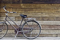 Old classic style bicycle park on old rough texture wood stripe floor and wall in background Royalty Free Stock Photos