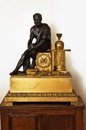 Old clock and statue gold antique clocks black on a pedestal Stock Photos