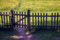 Old closed wooden gate with a fence in summer Sunny day Royalty Free Stock Photo
