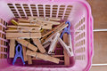Old clothespin in pink basket Stock Photos