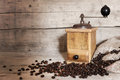 Old coffee grinder and beans on aged wooden background Royalty Free Stock Photo