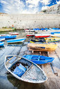 Old colored wooden boats in the small harbor. The Angevin castle in Gallipoli Royalty Free Stock Photo