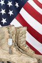 Old combat boots and dog tags with American flag Royalty Free Stock Photo