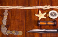 Old compass, money,  knife,  hourglass,  rope, starfish on   dark wood. Royalty Free Stock Photo