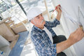 Old construction worker measuring wall Royalty Free Stock Photo