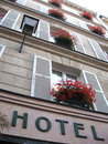 Old cosy hotel with flowers at the windows Stock Photography