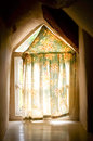 Old cottage window with light creeping in behind the curtain Royalty Free Stock Photo