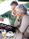 Old couple busy playing a game of backgammon Stock Photo