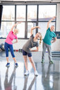 Old couple and girl in sportswear exercising in fitness class for kids and senior people