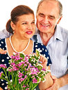 Old couple holding flower men embracing women sharpness on the bouquet Stock Images