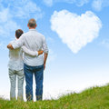 Old couple looking to heart cloud in sky on a hill a white a blue Royalty Free Stock Image