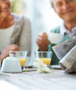 Old couple reading newspaper and having breakfast Royalty Free Stock Image