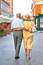Old couple walking at Piata Sfatului in Brasov, Romania. Royalty Free Stock Photo
