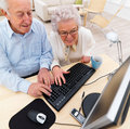 Old couple working together on computer Royalty Free Stock Photography
