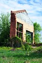 Old crumbling brick wall with window without glass, green trees and blue spring sky Royalty Free Stock Photo